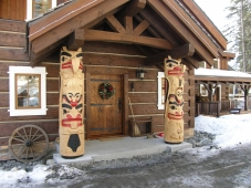 Two totems by artist Joe Ratushniak flank the entrance of this dovetail home near Glimpse Lake.
